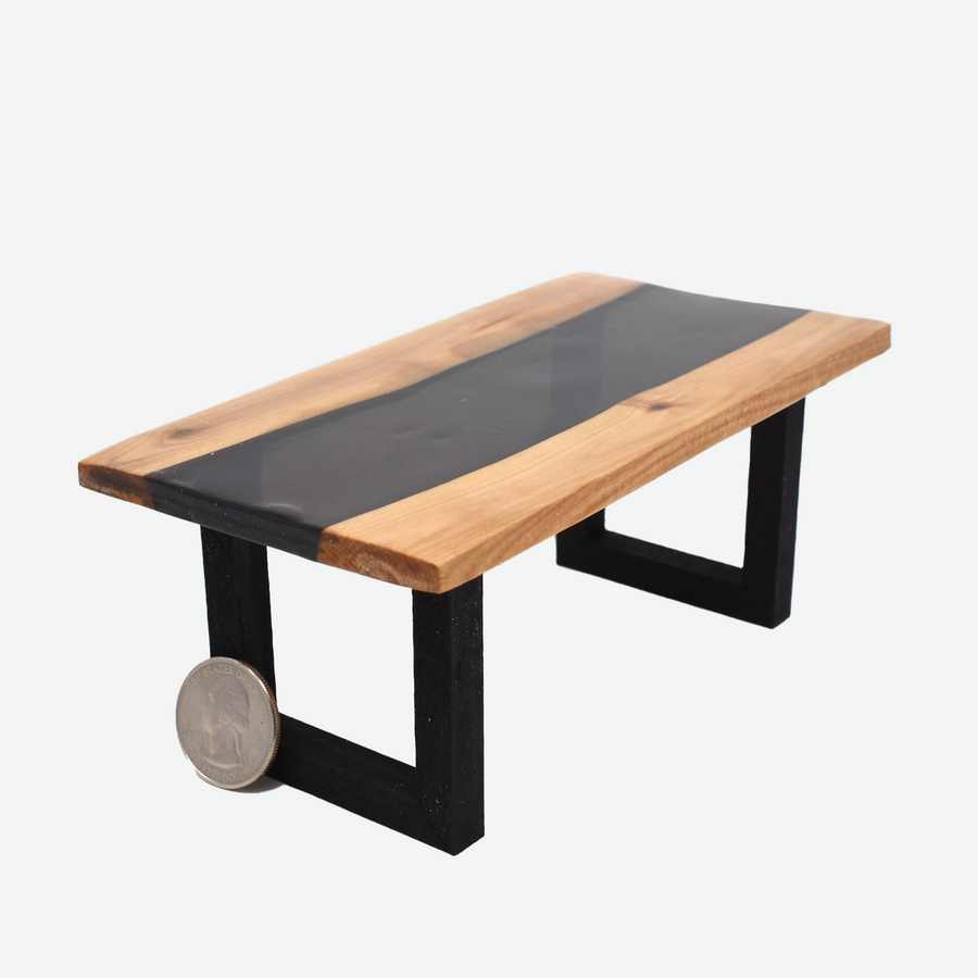 An angled front view of a 1:12 scale miniature black resin and wood river table with painted black legs. There is a quarter propped up in front of the left leg to show scale.