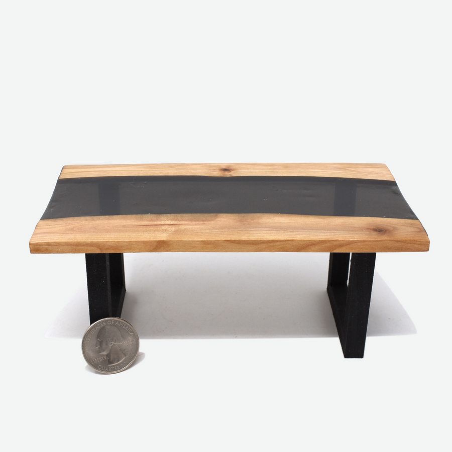 Front view of a 1:12 scale miniature black resin and wood river table with painted black legs. There is a quarter propped up in front of the left leg to show scale.