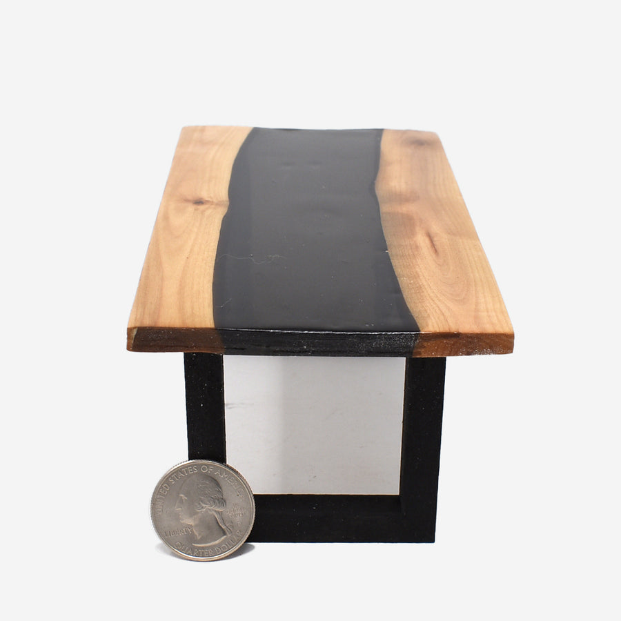 The side view of a 1:12 scale miniature black resin and wood river table with painted black legs. There is a quarter propped up in front of the left side of the leg to show scale.