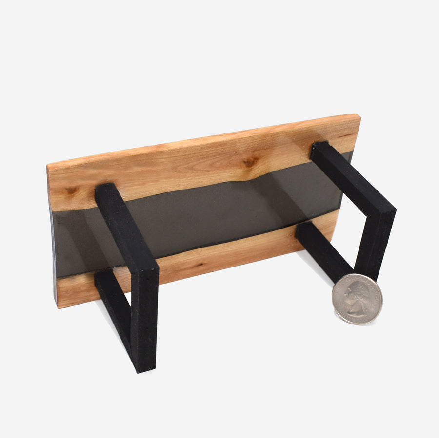 The bottom view of a 1:12 scale miniature black resin and wood river table with painted black legs. There is a quarter propped up in front of the right leg to show scale.