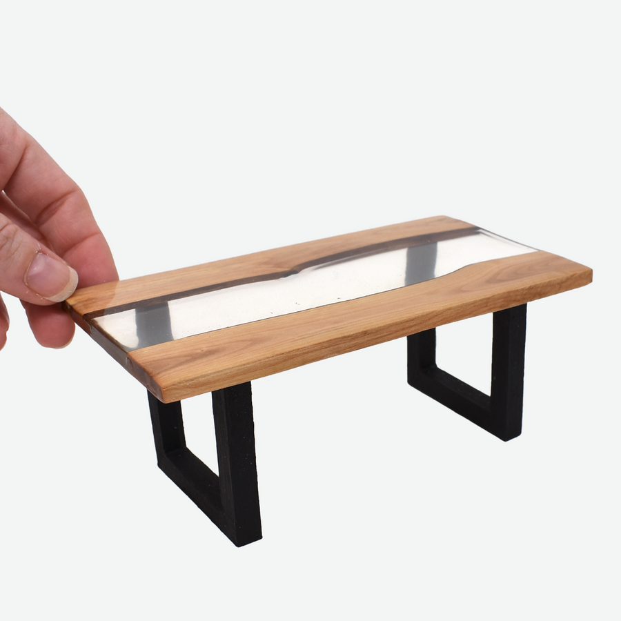 The angled front view of a 1:12 scale miniature clear resin and wood river table with painted black legs. There is a woman's hand holding the back left corner of the table to show scale.