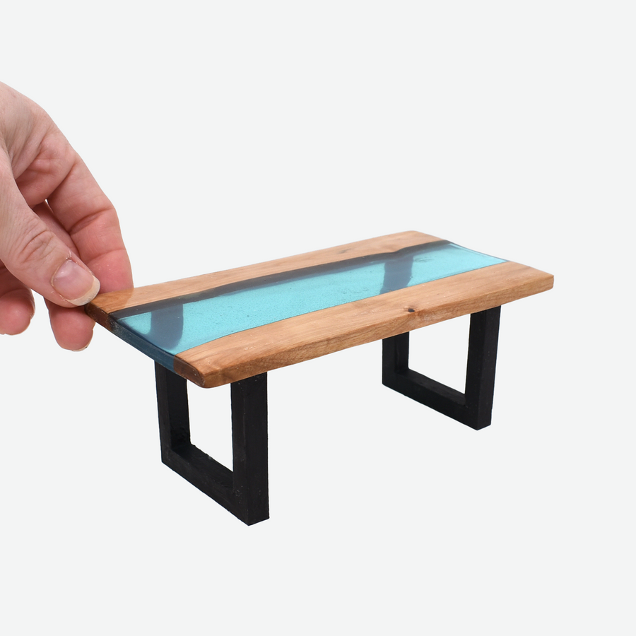 The angled front view of a 1:12 scale miniature teal colored resin river table with painted black legs. There is a woman's hand holding the back left corner of the table to show scale.
