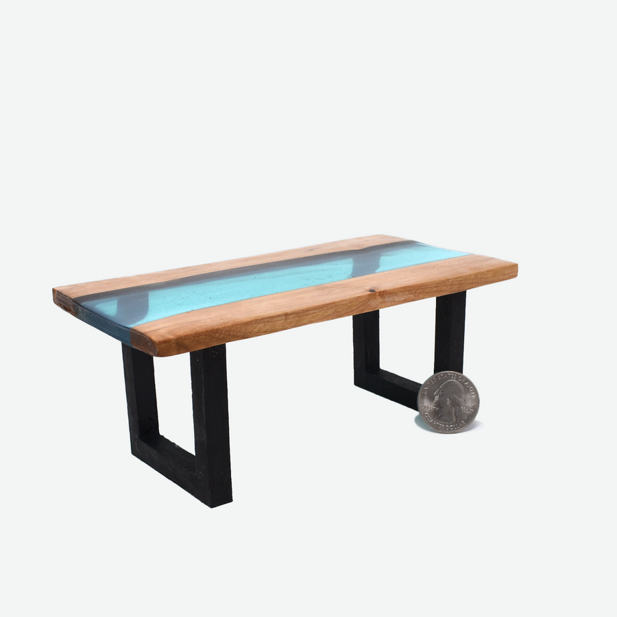 An angled front view of a 1:12 scale miniature teal colored resin river table with painted black legs. There is a quarter propped up in front of the front side of the right leg to show scale.