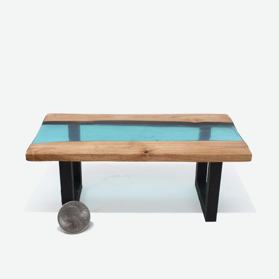 Front view of a 1:12 scale miniature teal colored resin river table with painted black legs. There is a quarter propped up in front of the left leg to show scale.