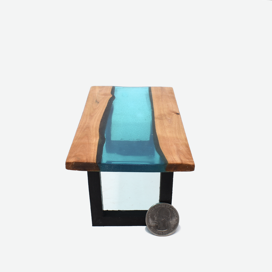 The side view of a 1:12 scale miniature teal colored resin river table with painted black legs. There is a quarter propped up in front of the right side of the leg to show scale.