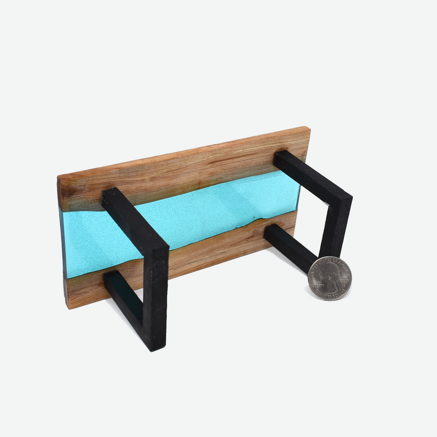 The bottom view of a 1:12 scale miniature teal colored resin river table with painted black legs. There is a quarter propped up in front of the right leg to show scale.