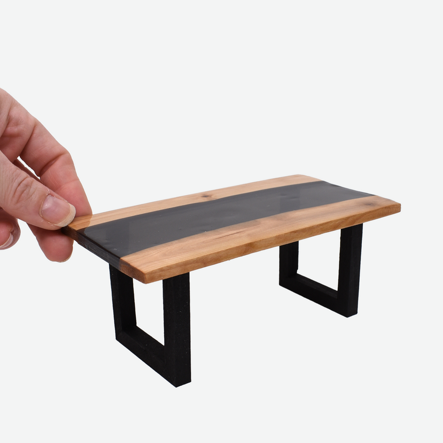 The angled front view of a 1:12 scale miniature black resin and wood river table with painted black legs. There is a woman's hand holding the back left corner of the table to show scale.