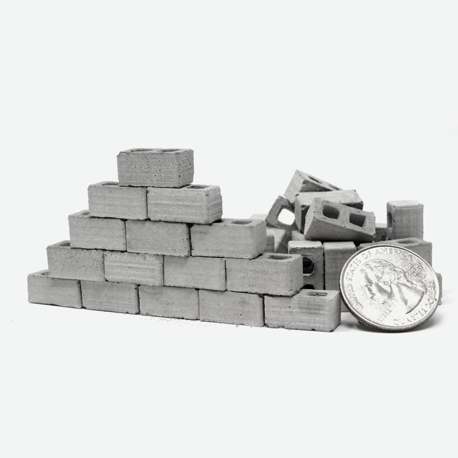 A small wall built with 1:24 scale mini cinder blocks with a quarter leaning against it for scale.