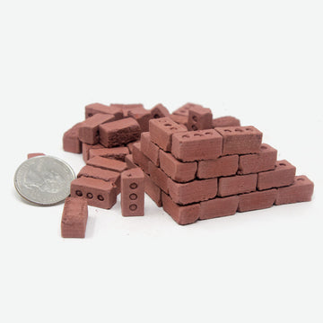 1:12 scale miniature red bricks sitting in a pile with quarter next to them for scale.