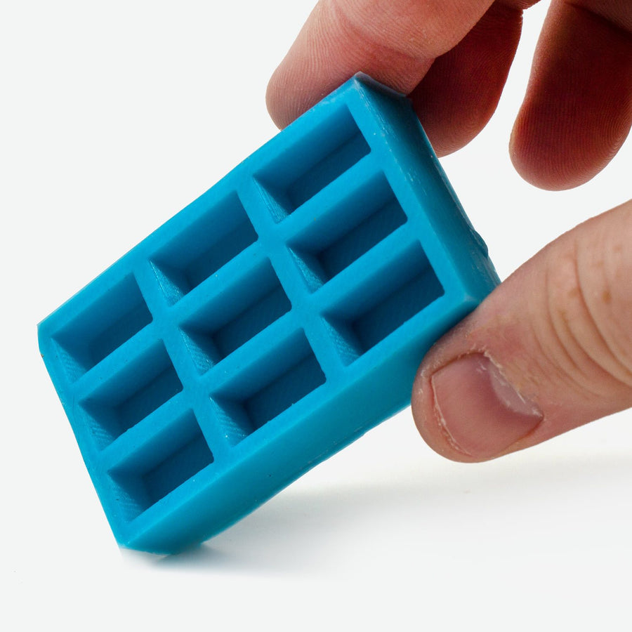 A 1:12 scale turquoise mold for red bricks is held by a pale white person's hand.