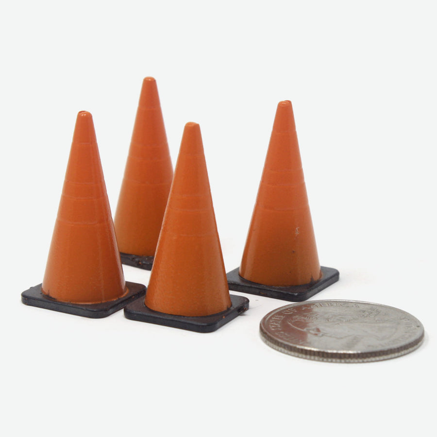 Four miniature road cones. They're orange with black bases. A quarter lays amongst them for scale.