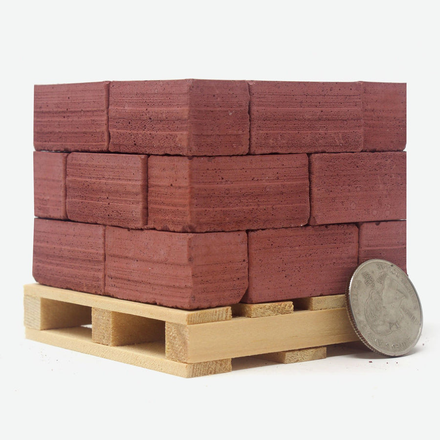 24 1:6 scale red bricks on an american pine pallet with a quarter leaning against them for scale.