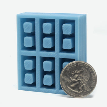 1:18 scale cinder block mold in teal with a quarter leaning against it for scale.