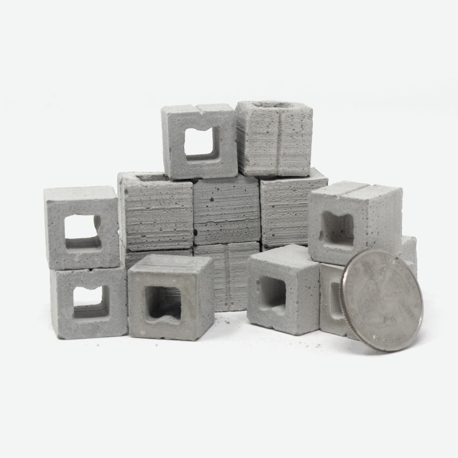 A pile of 1:12 scale half cinder blocks with a quarter leaning against them for scale.