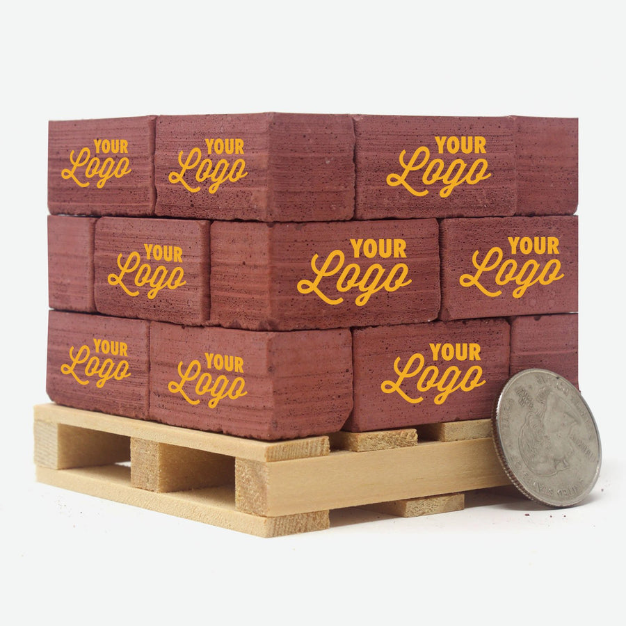 A pine pallet stacked with 1:6 scale red bricks. Each one has a one color logo on them that says
