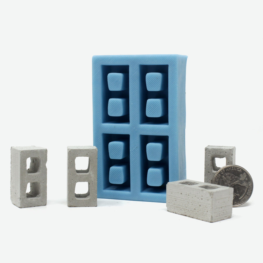 A teal silicone mold for mini cinder blocks with four cinder blocks surrounding it and a quarter leaning against it for scale.