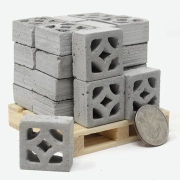 24 cement empress style breeze blocks on a miniature pallet with a quarter for scale. One mini breeze block is sitting in front of it all.