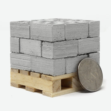 24 1:18 scale mini cinder blocks on a small pine pallet with a quarter leaning against them for scale.