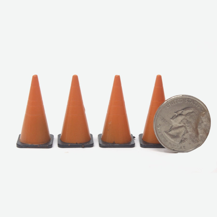Four miniature road cones stand in a straight line. They're orange with black bases. A quarter lays amongst them for scale.