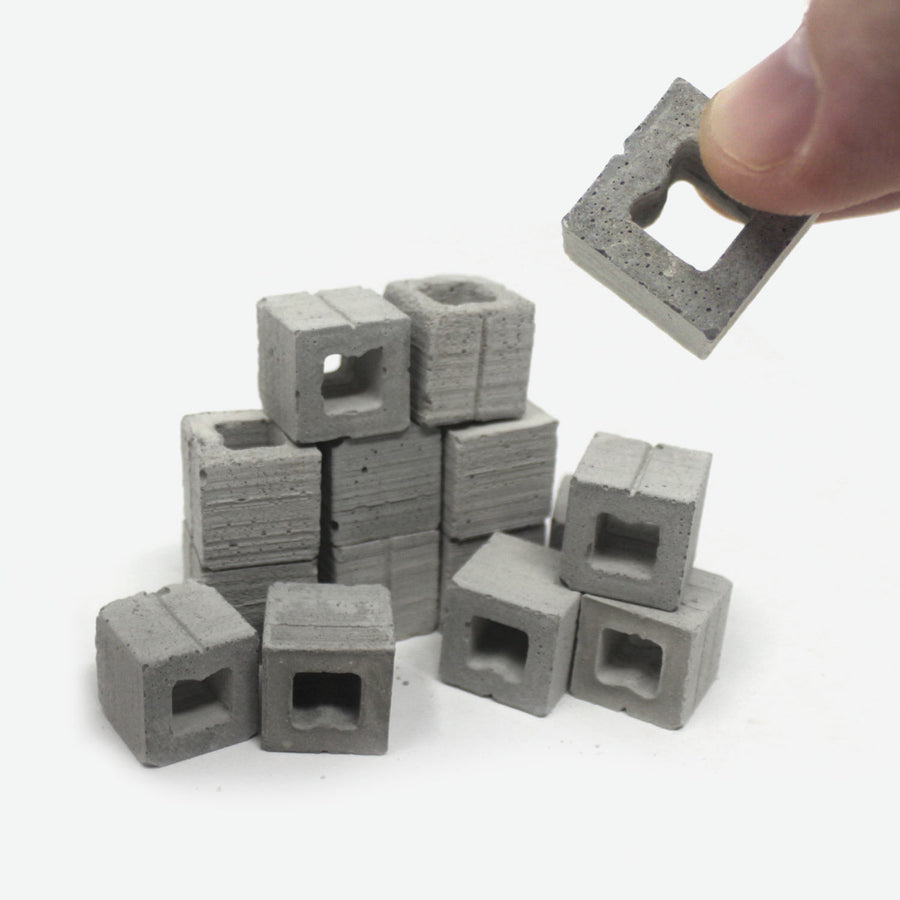 A pile of 1:12 scale half cinder blocks with a hand grabbing one and holding it closer to the camera.