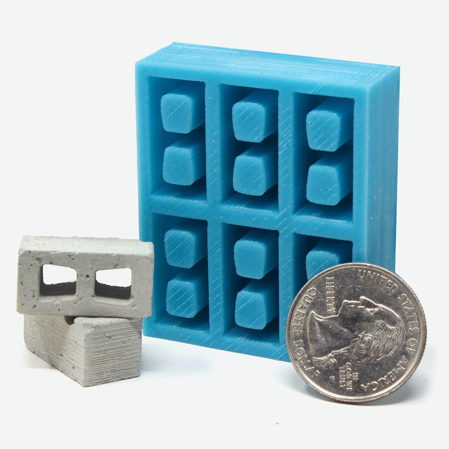 1:18 scale cinder block mold in teal with a quarter leaning against it for scale. Two cinder blocks lay next to it.