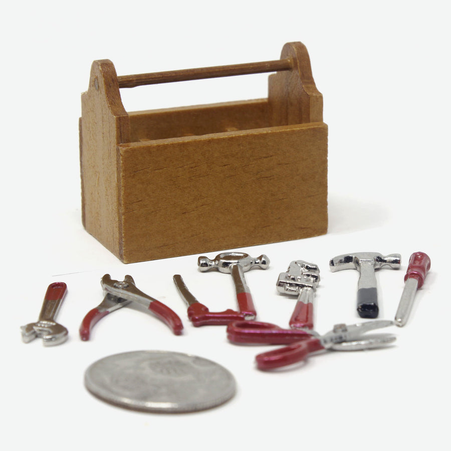 A miniature wooden toolbox with a quarter leaning against it for scale. The tools are laid out on the ground in front of it.