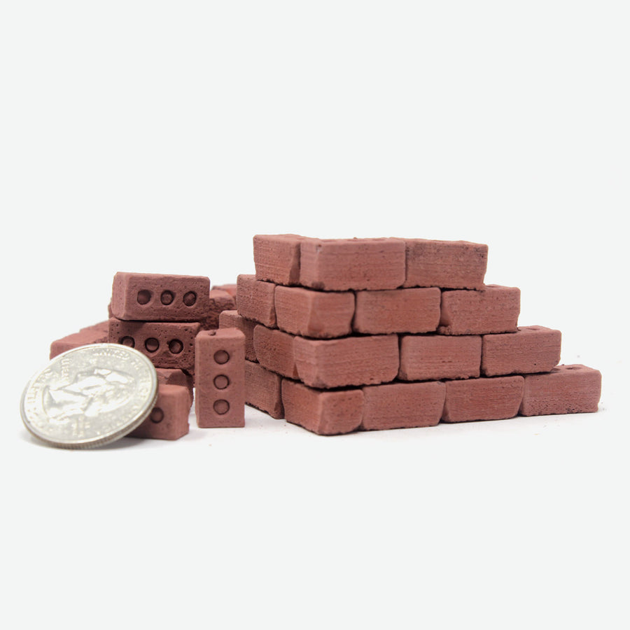 1:12 scale miniature red bricks sitting in a pile next to a brick wall with quarter next to them for scale.
