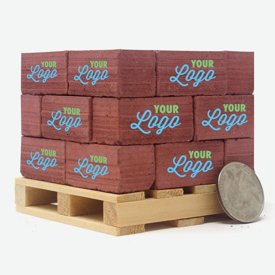 A pine pallet stacked with 1:6 scale red bricks. Each one has a two color logo on them that says