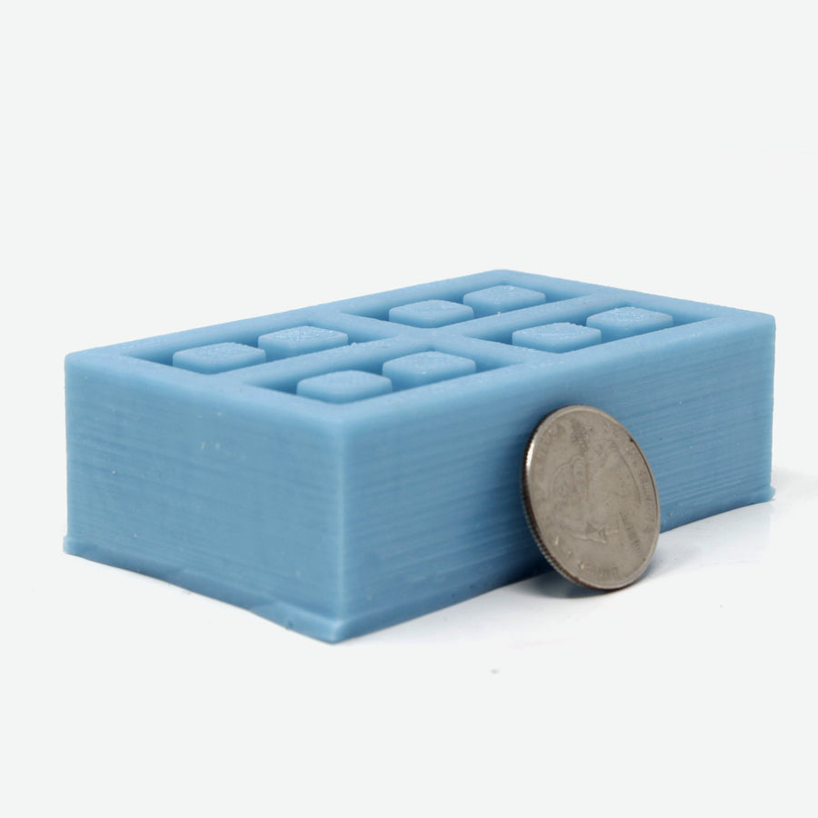 A teal silicone mold for mini cinder blocks with a quarter leaning against it for scale.