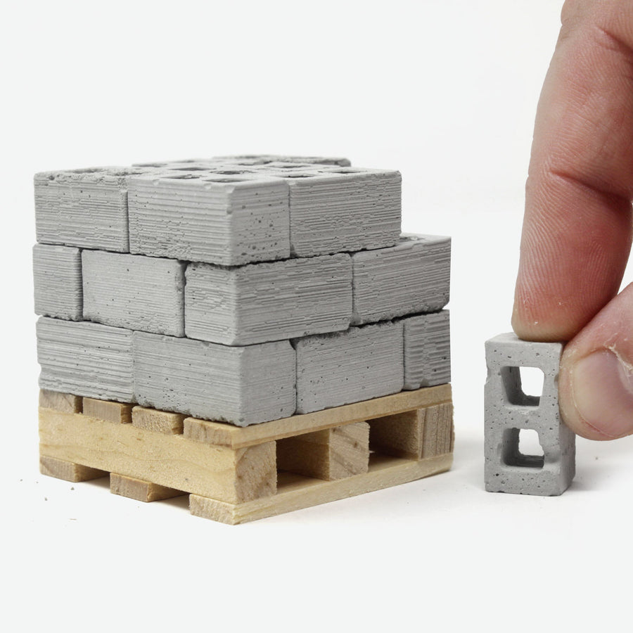 24 1:18 scale mini cinder blocks on a small pine pallet with a hand grabbing one to the side.
