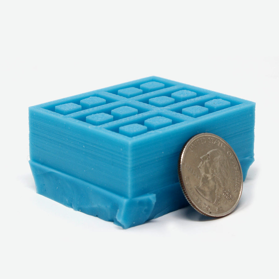 1:18 scale cinder block mold in teal with a quarter leaning against it for scale. The mold is facing upward.