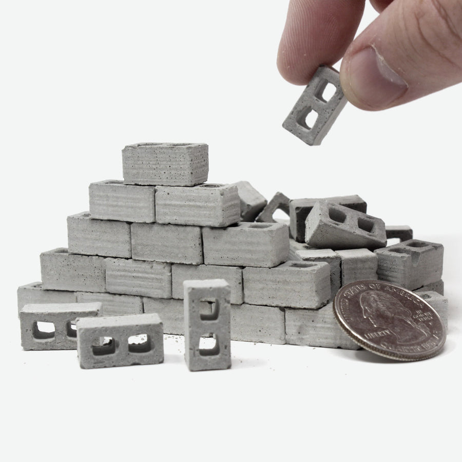 A small wall built with 1:24 scale mini cinder blocks with a quarter leaning against it for scale. A hand is reaching down to grab one of the cinder blocks.