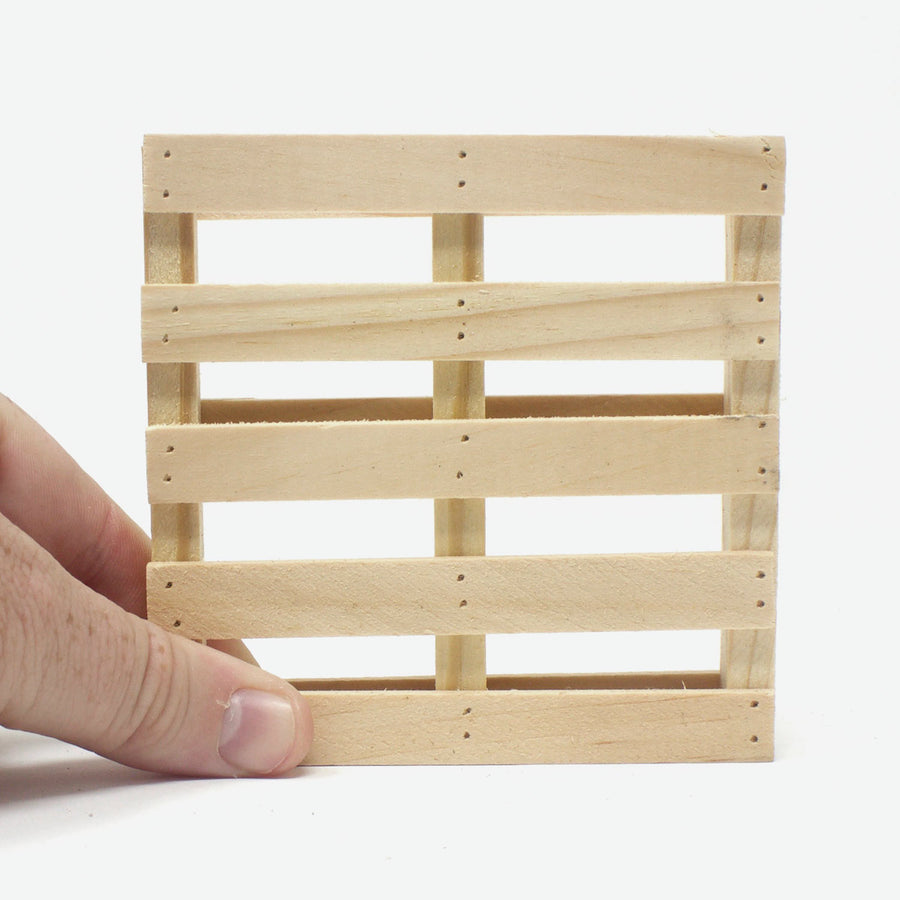 A hand holding up a single miniature pallet coaster in pine.