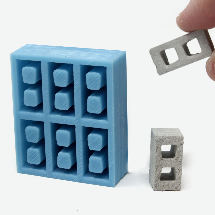 1:18 scale cinder block mold in teal with a hand grabbing a mini cinder block from it.
