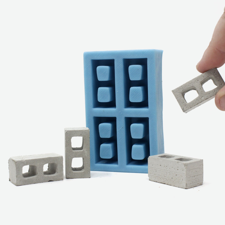 A teal silicone mold for mini cinder blocks with a hand grabbing a mini cinder block from it.