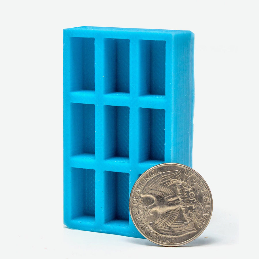 A 1:12 scale turquoise mold for red bricks stands vertically with a US quarter leaning against it for scale.