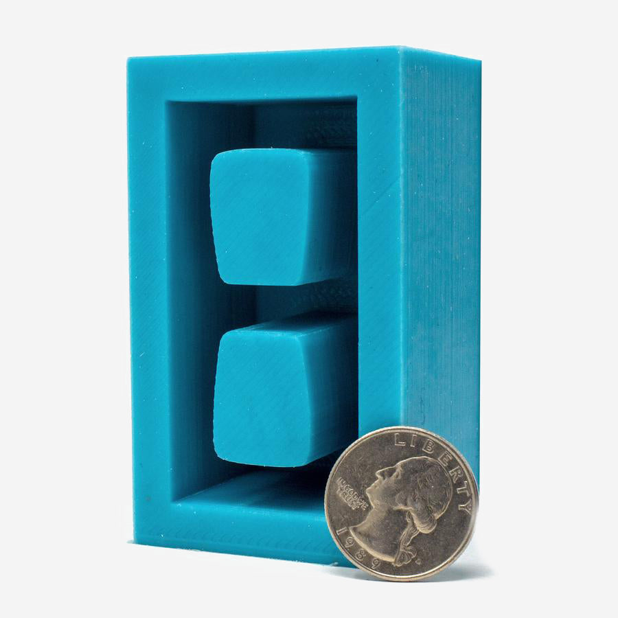 1:6 scale cinder block mold that makes one piece. Made of turquoise silicon with a quarter next to it for scale, along with a 1:6 scale cinder block.