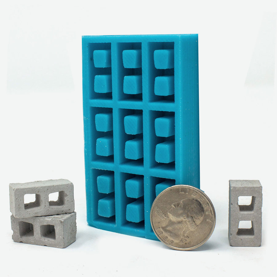1:18 scale mini cinder block mold in turquoise with a quarter for scale.