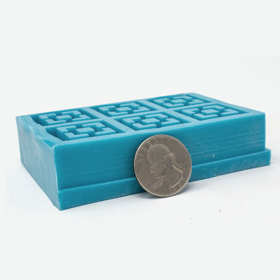 Vista vue breeze block 6 piece mold made out of turquoise silicone. A quarter lays against it for scale.