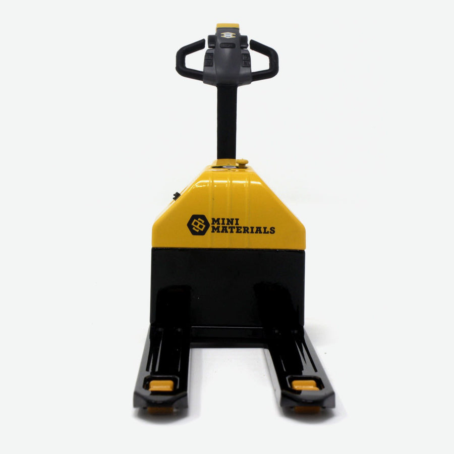 A 1:12 scale pallet jack that is black and yellow. A quarter lays against it for scale. It is facing towards the camera.
