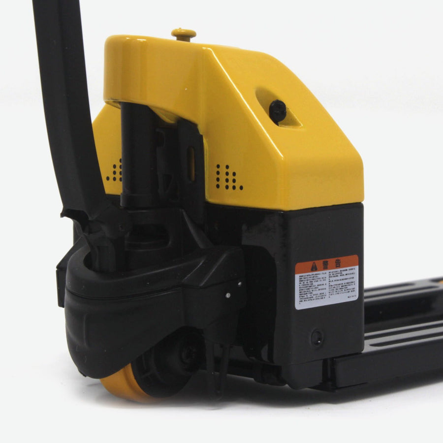 A zoomed in shot of the back of a 1:12 scale pallet jack that is black and yellow. A quarter lays against it for scale.