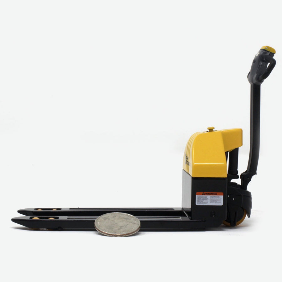 A side view of a 1:12 scale pallet jack that is black and yellow. A quarter lays against it for scale.