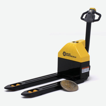 A 1:12 scale pallet jack that is black and yellow. A quarter lays against it for scale.