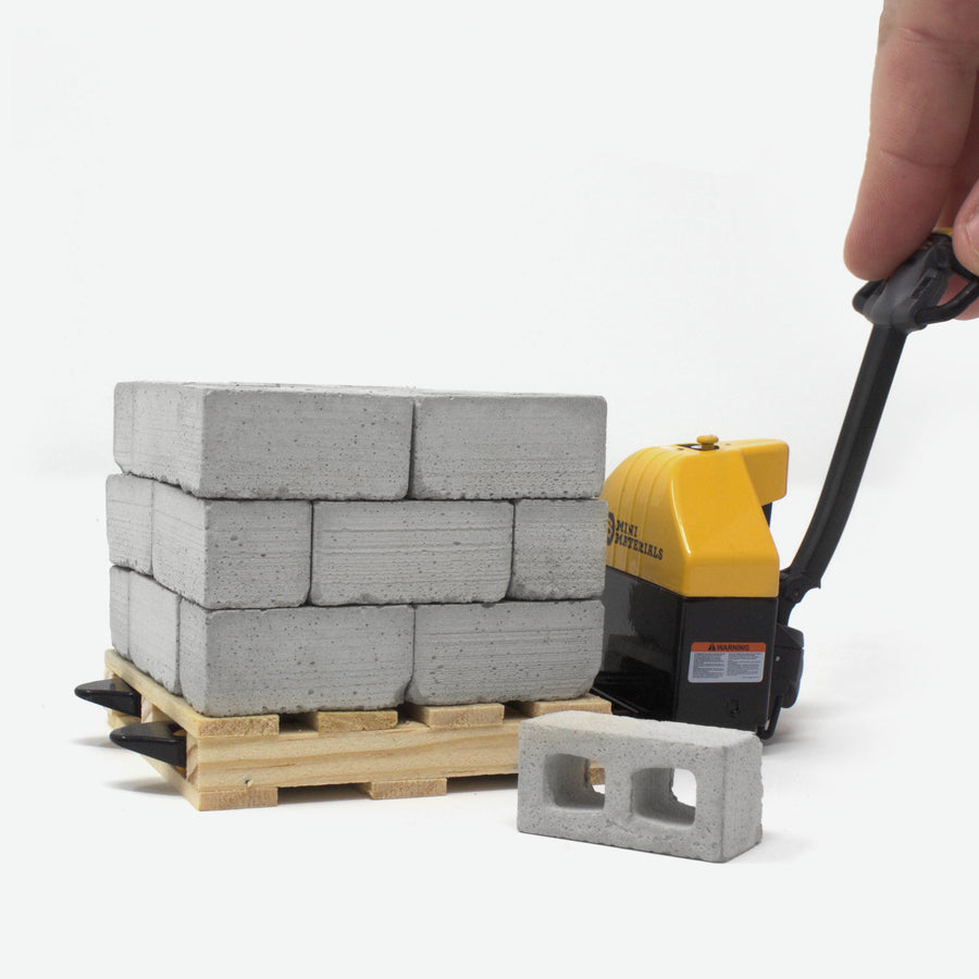 A 1:12 scale pallet jack that is black and yellow. It is pushing a pallet of mini cinder blocks with a hand guiding it. A block is laying on the ground.