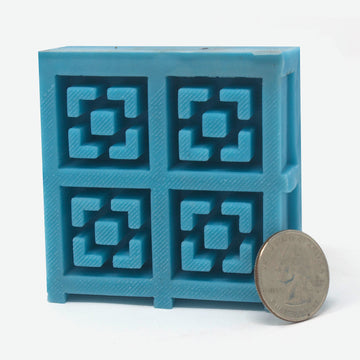 A 2x2 mold of 1:12 scale breeze blocks made of turquoise silicone standing vertically. A quarter rests against it for scale.
