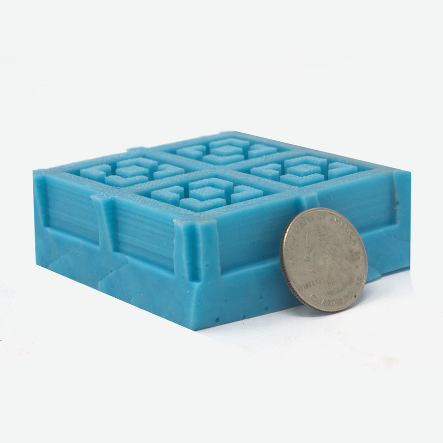 A 2x2 mold of 1:12 scale breeze blocks made of turquoise silicone laying down facing up. A quarter rests against it for scale.