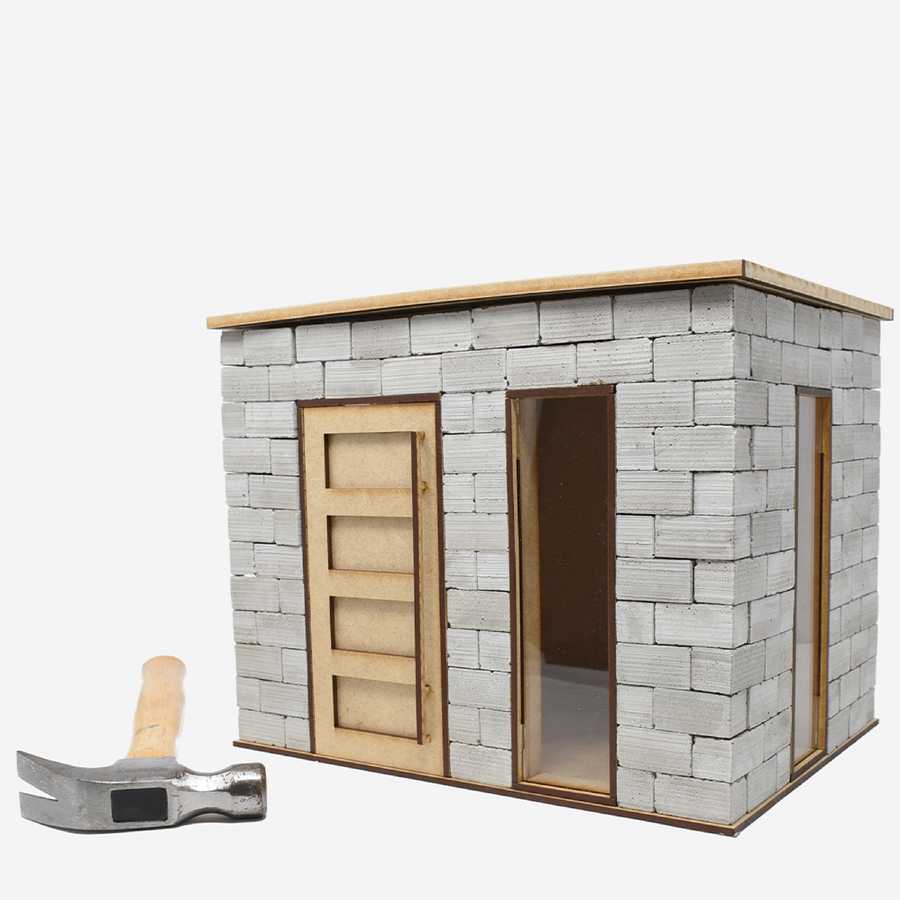 This shows the front and right side of the 1:12 scale miniature cinder block build kit. A hammer is laying on the left of the kit to show scale.