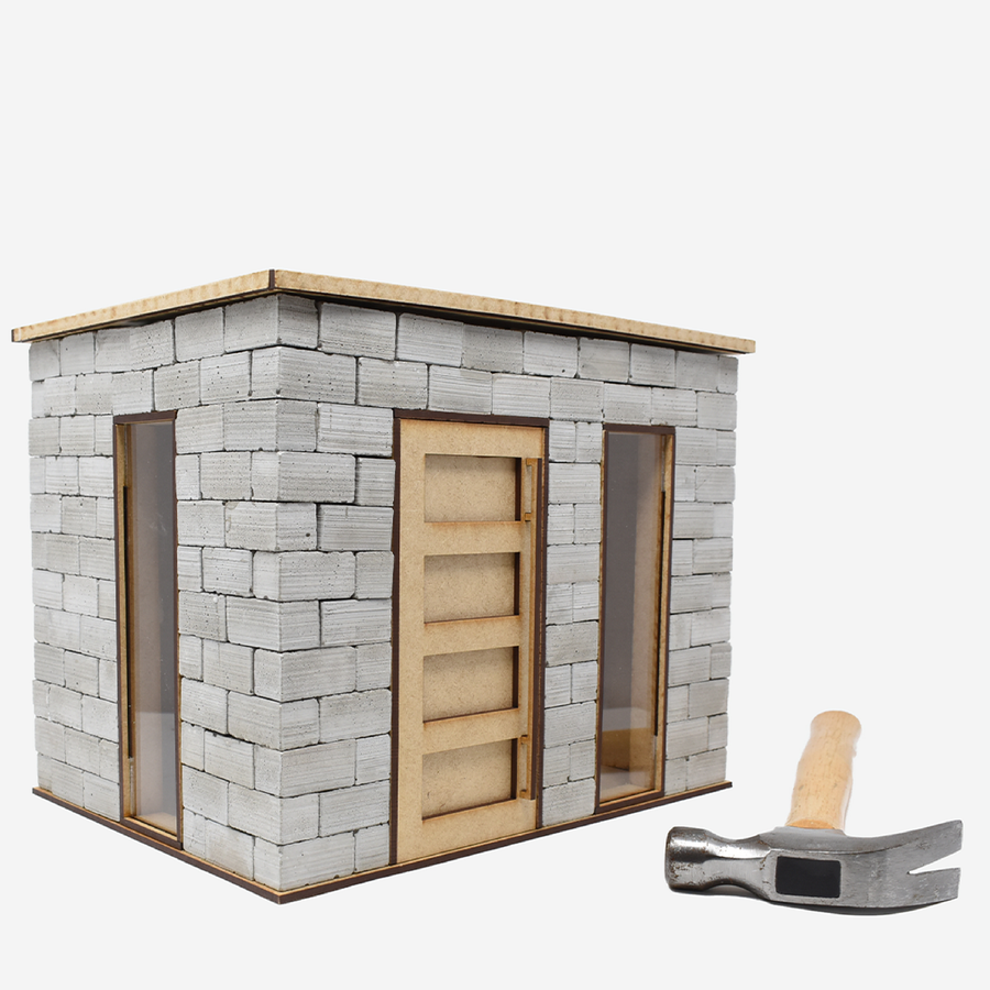 The left side of the 1:12 scale miniature cinder block build kit. A hammer is laying in front of the kit to show scale.