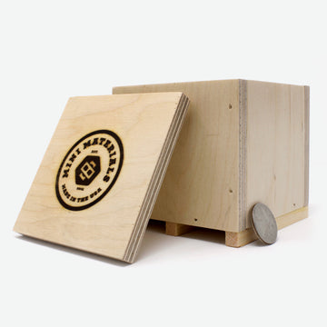 A pine crate with lid laying against with an engraved Mini Materials logo. A quarter lays against it on the right side for scale.