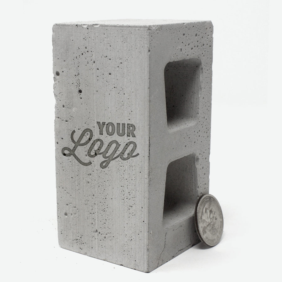 A 1:4 scale cinder block  standing vertically with a quarter leaning against it. The words